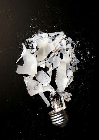 Smashed incandescent light bulb with glass shards on dark background