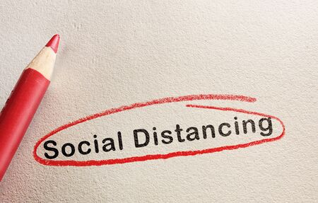 Social Distancing text circled in red pencil on textured paper 免版税图像