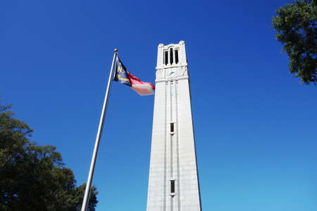 The bell tower and NC state flag on the campus of NC State University in Raleigh