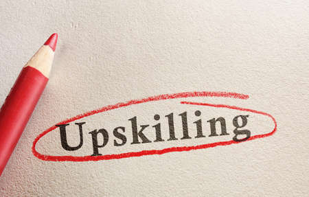 Upskilling text on paper circled in red pencil - job training concept