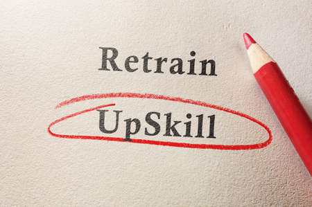 Upskill circled in red pencil below Retrain text on textured paper  --  job training concept