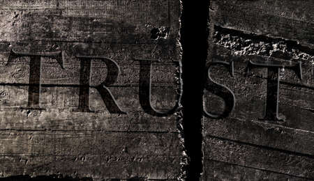 Trust text with a crack in the middle on textured stone surface  -- broken promise concept