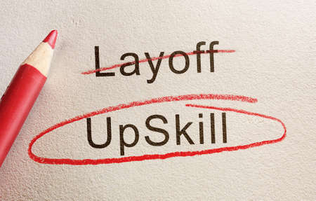Upskill text circled in red pencil below Layoff, workforce retraining concept