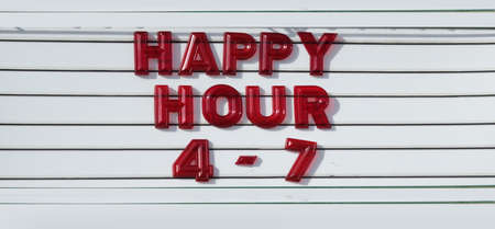 Happy Hour spelled out in red letters on a vintage sign of a bar