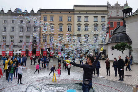 KRAKOW,POLAND - 9-22-2017: A street performer entertains the crowd with bubbles in the main square of Krakow Poland