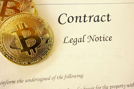 Gold bitcoin cyptocurrency and a legal contract document Standard-Bild