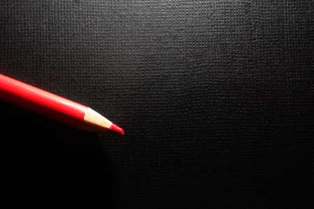 Red pencil on black textured paper background with blank copy space Standard-Bild