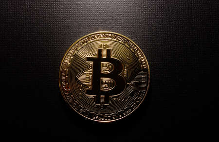 Gold bitcoin on black textured background