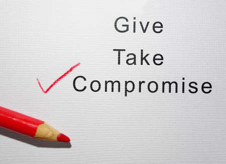 Give Take and Compromise text with red pencil check mark on paper