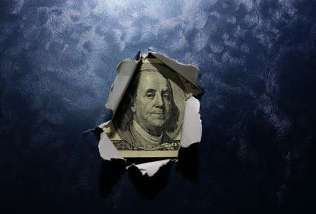 Hole ripped in textured metallic background surface with hundred dollar bill