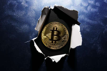 Gold bitcoin with a ripped hole on blue textured background