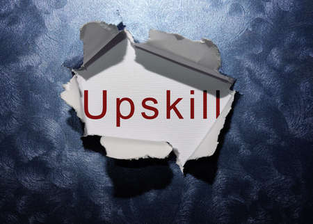 Upskill text revealed in ripped blue paper background .