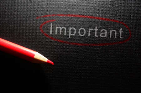 Important text circled in red pencil on black textured paper background Standard-Bild