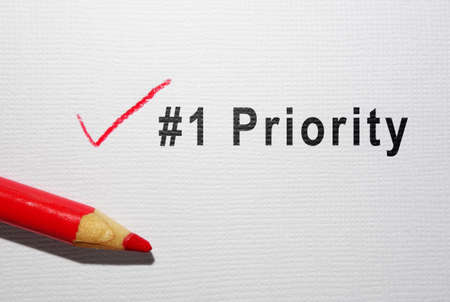 Number one Priority text with red pencil checkmark on paper