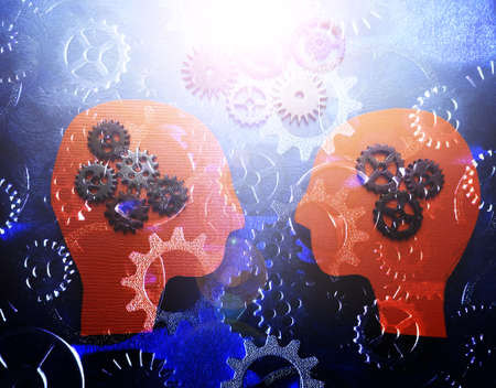 Two heads facing each other with gears background -- teamwork and cooperation concept Standard-Bild