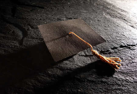 Miniature graduation - education cap on dark textured surface Standard-Bild