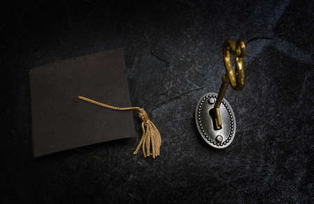 Gold key opening a lock, and graduation cap