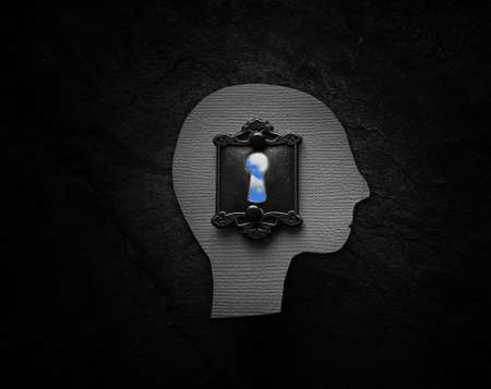 Textured head figure with vintage lock and blue sky keyhole on dark textured background