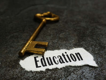 Education message with gold key on dark background
