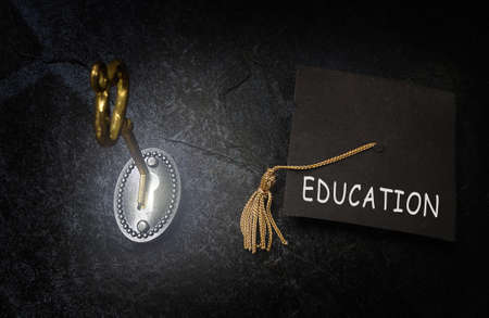 Gold key opening a lock, and Education graduation cap Standard-Bild