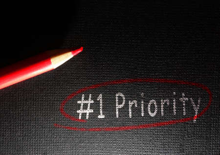 Number one priority circled in red pencil on black textured paper background