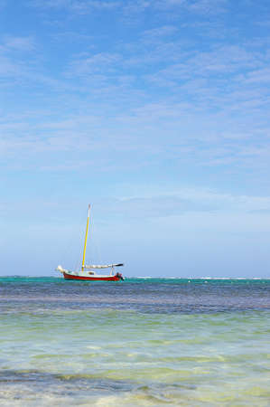 A sailboat sitting just off shore along the beach in Belize Standard-Bild