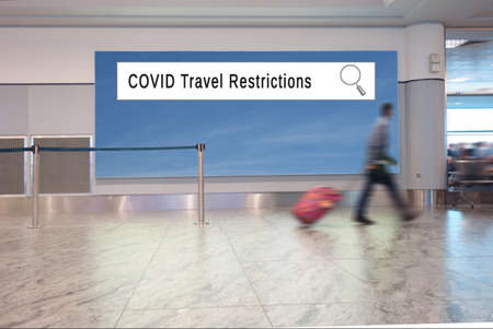 A man with a suitcase walks in an airport, with COVID Travel Restrictions internet search window