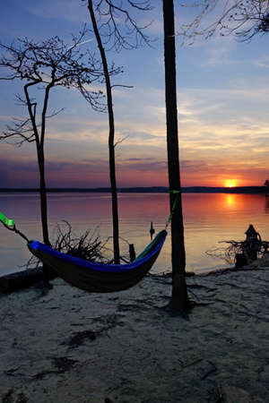 A hammock hanging in the trees at sunset on the shore of Jordan Lake State Park campground near Raleigh North Carolina