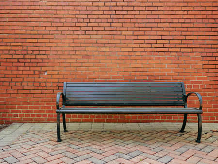 An empty metal park bench in front of a blank brick wall Stock fotó