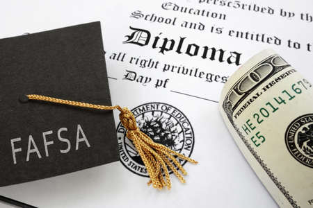FAFSA (Free Application for Federal Student Aid) text on graduation cap with diploma and money -- financial aid concept