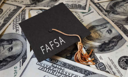 FAFSA (Free Application for Federal Student Aid) text on graduation cap and money -- financial aid concept Stock fotó