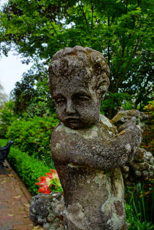 A weathered cherub statue in one of many landscaped gardens of Charleston