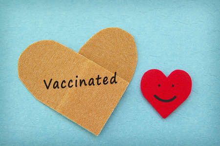 Vaccinated text on a heart shaped bandage with red smile heart Stock fotó