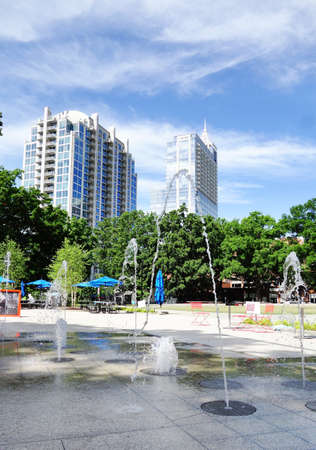Moore Square Park with splashpad fountain in the foreground and downtown Raleigh buildings in the distance