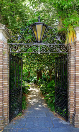 Wrought iron gate open to a path in Charleston SC, leading to one of the city's many lush gardens Stock fotó