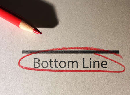 Bottom Line text circled in red pencil on textured paper surface