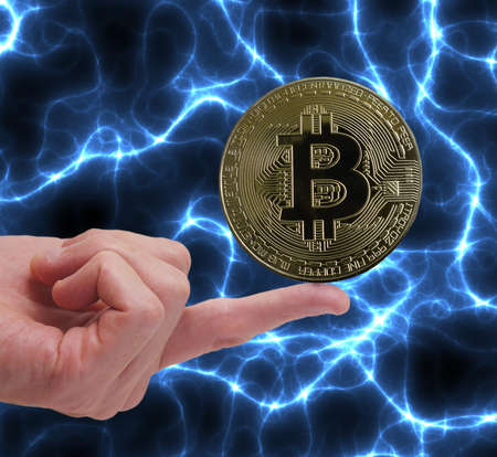Bitcoin cryptocurrency coin balancing on a finger with blue energy background Stock fotó