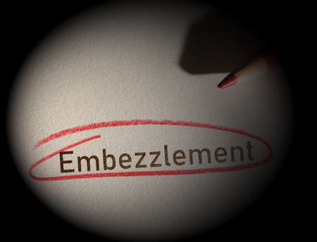 Embezzlement text circled in red pencil on a dark background Stock fotó