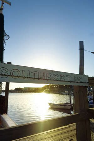 A weathered Southport , NC sign hangs at a dock in the marina on the Cape Fear River