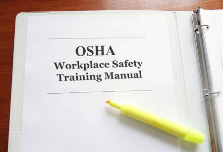 OSHA (Ocuupational Safety and Health Administration) manual on a desk -- safe workplace concept
