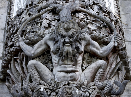 grotesque: Carved stone figure of a sea monster in a wall at the Palacio da Pena, Sintra, Portugal. Pena National Palace (Palacio Nacional da Pena) the oldest palace inspired by European Romanticism. Located on the top of a hill above the town of Sintra, Portugal. U Editorial