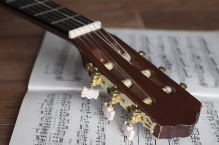 guitar tuner: Guitar headstock with notes on wooden background, close up, focus on headstock