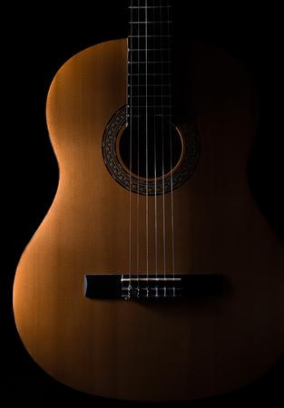 Guitare classique sur un fond sombre guitare classique sur un fond sombre. Le bois de guitare est brun clair avec un beau grain.