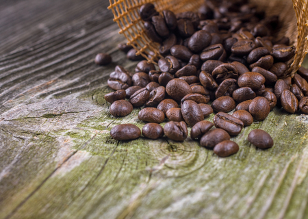 sho: Coffee beans in coffee bag on old green wooden surface
