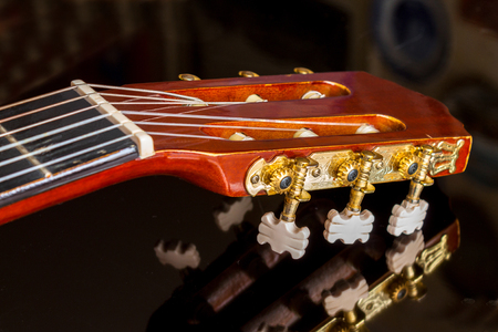Guitar headstock on black reflecting surface, close up, with very shallow depth of field, focus on tuning pegs 스톡 콘텐츠