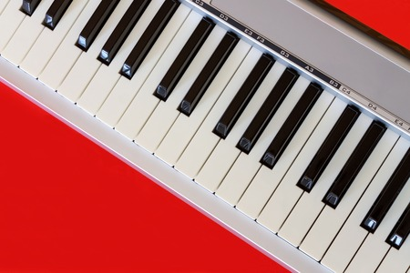 Top view on digital piano keyboard on the red bacground