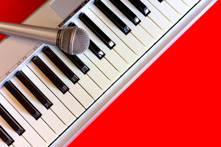 Top view on digital piano keyboard with microphone on the red bacground