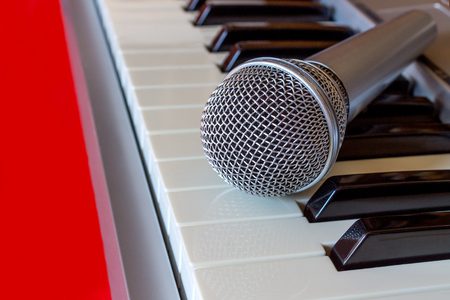 Close up of digital piano keyboard with microphone on the red bacground