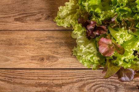 Fresh mixed salad field greens piled on wooden table Stock Photo