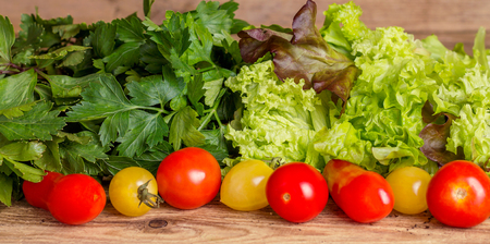 Red and yellow tomatoes, fragrant herbs and lettuce leaves